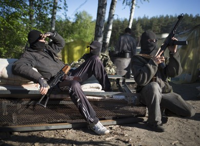 Pro-Russian armed men rest as they guard a checkpoint near Krasny Linam village outside Slovyansk.