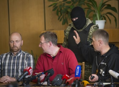 Vacheslav Ponomarev, the self-proclaimed mayor of Slovyansk, right, speaks to a pro-Russian gunman, as two of foreign military observer, one of them Axel Schneider of Germany, center, look to each other during a press conference in city hall, of Slovyansk.