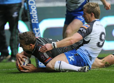 Ashley Beck crosses for the Ospreys despite the attention of Kieran Marmion.