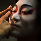 A professional artisan of kabuki makeup paints a man's face with a pattern of makeup called