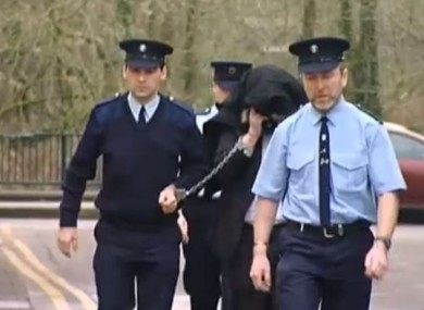 McGrath being led away from court during the murder case of Sylvia Roche Kelly.
