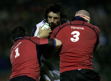 Sale Shark's Sebastien Chabal is stopped by Munster's Marcus Horan and John Hayes during a 2006 Heineken Cup match.