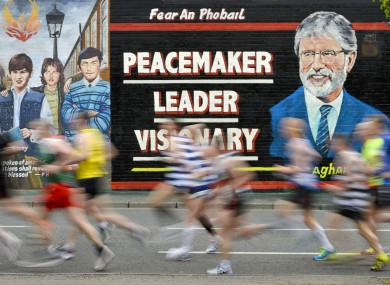 Runners pass a mural on the Falls Road.