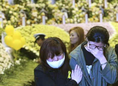 Relatives of a passenger aboard the sunken ferry Sewol weep as they pay tribute to the victims of the ship at a group memorial altar in Ansan, South Korea