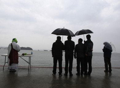 A Buddhist Monk and others pray for the safe return of passengers of the sunken ferry Sewol at a port in Jindo, South Korea.