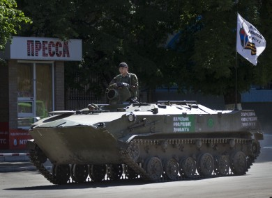 A pro-Russian militant sits atop an armored personal carrier.