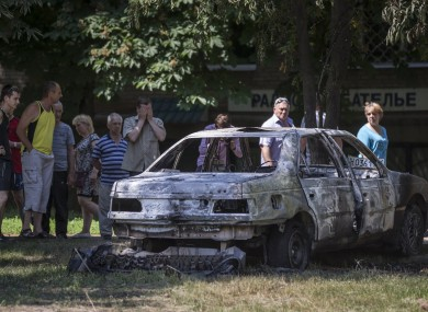 Local people look at a burnt-out car following a shelling from Ukrainian government forces, in Slovyansk