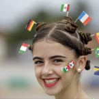 A fan donning miniature national flags representing Italy, Germany, Mexico, the Netherlands, Spain, Brazil and Bosnia in her hair smiles.<span class=