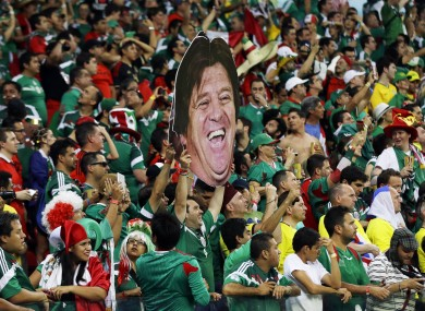 Mexico fans in full spirits with a poster of manager Miguel Herrera's head at the Arena Pernambuco in Recife last night.