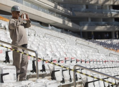A worker takes a picture at the Itaquerao, one of six stadiums that were supposed to be finished by the end of 2013, but a crane collapse that killed two workers in November caused delays (File photo)