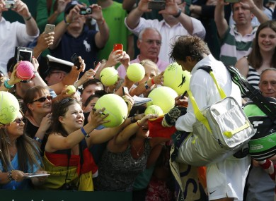 Rafael Nadal sings autographs after defeating Martin Klizan of Slovakia.