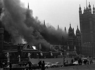 Flames leap amid the smoke pouring from the House of Commons after the bomb blast in the crypt chapel.