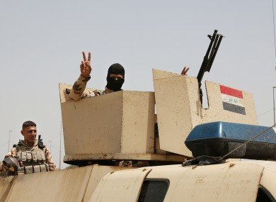 An Iraqi soldier flashes a V for victory sign in Baghdad.