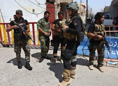 A member of Iraq's Special Weapons and Tactics Team (SWAT), center, stands with other Iraqi Shiite gunmen from al-Mahdi army, at a street linked to a Shiite mosque, in the northern oil rich province of Kirkuk.