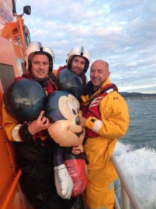 Mickey Mouse being brought safely to shore.