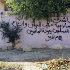 An empty house of a Christian family  in Mosul with Arabic writing that reads,