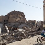A bicyclist rides by the destroyed old Mosque of The Prophet Jirjis in central Mosul, Iraq, Sunday, July 27, 2014. The revered Muslim shrine was destroyed on Sunday by militants who overran the city in June and imposed their harsh interpretation of Islamic law. (AP Photo)<span class=
