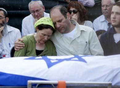 Avi and Rachel Fraenkel embrace during the funeral of their son, Naftali.