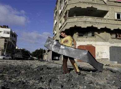 A Palestinian man carries rubble near a Hamas training camp following an Israeli air strike on it early morning in Gaza City.