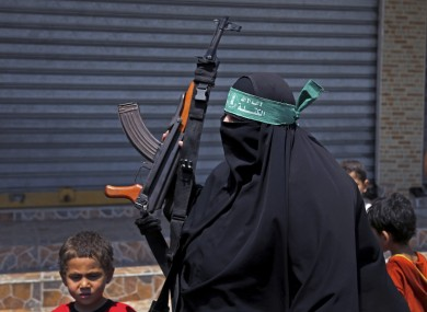 A Hamas supporter holds an AK-47 as she attends a demonstration against the Israeli military operations in the West Bank.