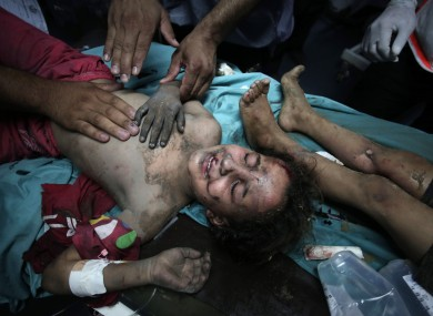 Palestinian medics comfort an injured girl at the Shifa hospital after an Israeli missile strike in Gaza City.