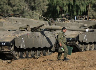 An Israeli soldier walks past tanks near the Israel and Gaza border.