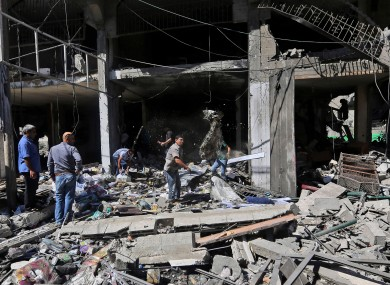 Palestinians inspect the rubble of a building that was hit today by an Israeli missile strike