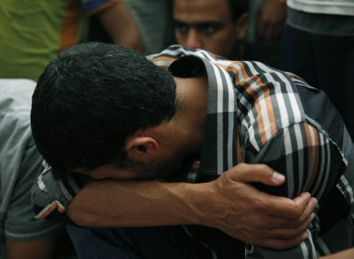 A Palestinian mourner cries at a mosque as he sits next to the bodies of Mousa Abu Muamer, 56, and his son Saddam, 27, who were killed in an overnight Israeli missile strike at their house in the Gaza Strip.