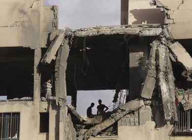 Palestinian youths inspect a damaged building after it was hit by an Israeli airstrike in Beit Lahiya, northern Gaza Strip.