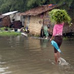 A woman carries water-cress as she wades through a flooded road following heavy rains in outskirts of Yangon, Myanmar. Photographed by: Khin Maung Win <span class=