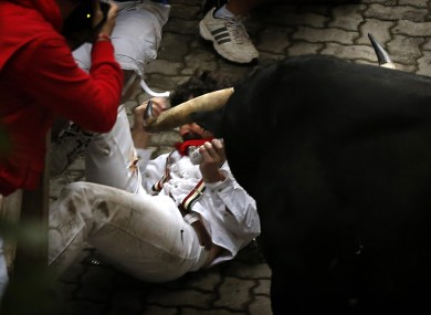 Bill Hillman struggles with a bull after being gored at the San Fermin festival in Pamplona.