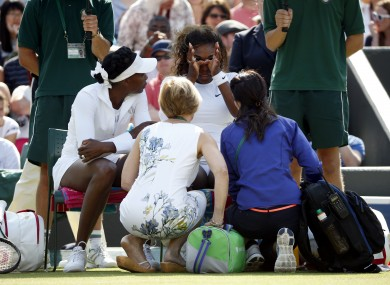 Serena (right) receives treatment alongside sister Venus Williams before their doubles match.
