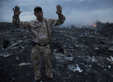 A man gestures at a crash site of a passenger plane near the village of Grabovo, Ukraine.