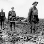 First Battle of Passchendaele. Two guardsmen bringing in a wounded comrade on a stretcher, near Langemarck, October 1917.<span class=
