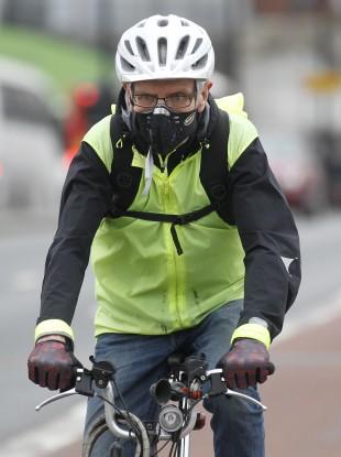 A cyclist wearing a mask cycles across London Bridge.