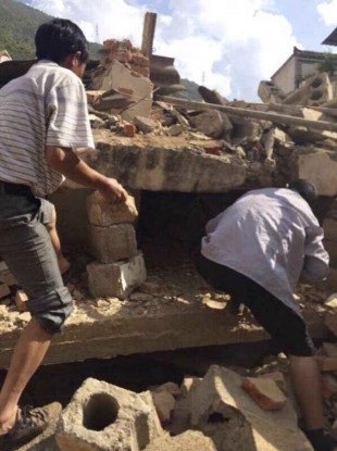In this photo taken by cellphone and released by China's Xinhua News Agency, men at rubbles of buildings look for survivors after an earthquake in Ludian County of Zhaotong City.