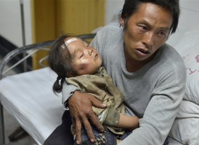 A man holds an injured child receiving medical treatment at a hospital following an earthquake in Ludian county in southwest China's Yunnan province