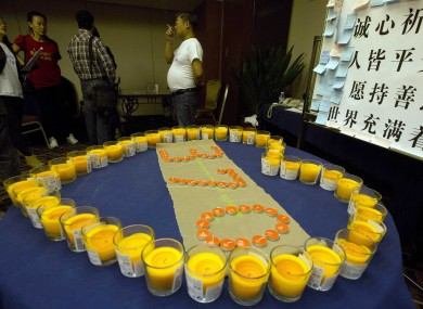 File photo dated 3 April 2014: Relatives of Chinese passengers on board the missing flight stand by a candle memorial in a prayer room in Beijing.
