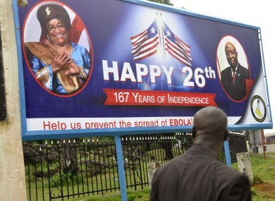 A billboard reading 'Help us prevent the spread of Ebola, center, with the face of Liberia President Ellen Johnson Sirleaf, left, in the city of Monrovia, Liberia.