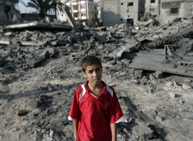 A Palestinian boy stands on debris from destroyed houses hit by an overnight Israeli strike.