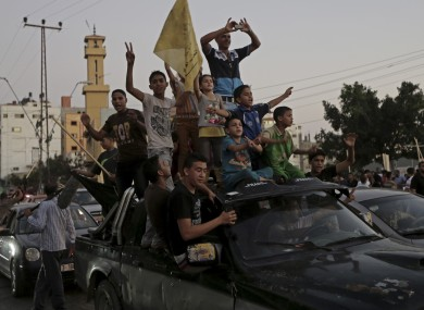 Palestinians celebrate the cease-fire between Palestinians and Israelis at the main road in Gaza.