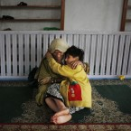 A flood affected Kashmiri girl comforts her grandmother at a mosque in Srinagar.<span class=