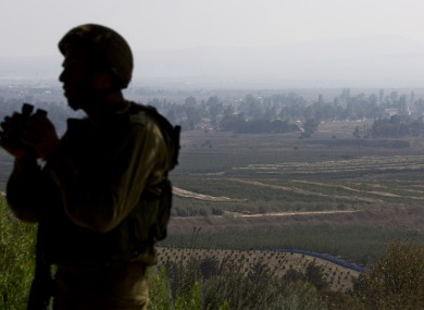 An Israeli soldier observes Syria's Quneitra province at an observation point in the Israeli-controlled Golan Heights.