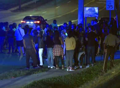 Crowd gathers near the scene where a police officer was shot.