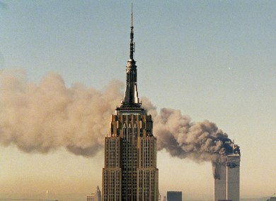 The twin towers of the World Trade Center burn behind the Empire State Building in New York.