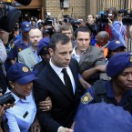 Escorted by police and security, Oscar Pistorius leaves the court in Pretoria.<span class=