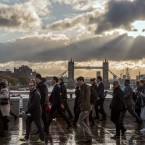 Commuters pictured crossing London bridge at the tail end of hurricane Gonzalo.<span class=