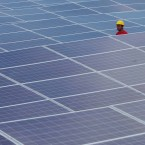 A technician walks through solar panels at the government-run Fotovoltaica Solar Plant in Cobija, in the Amazon area of northern Bolivia.<span class=