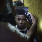 A young man gets his hair cut at a party in Rio de Janeiro, Brazil.<span class=
