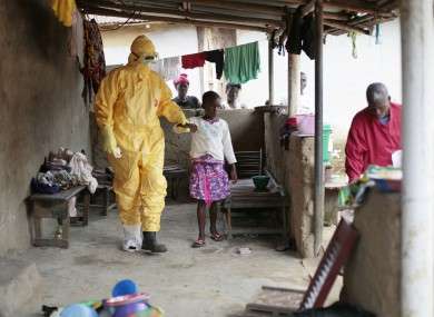 Nowa Paye, 9, is taken to an ambulance after showing signs of Ebola infection.